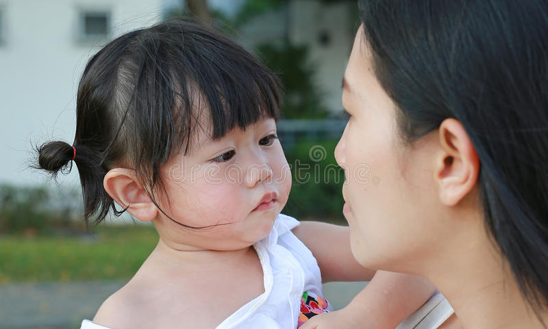 Mother carrying her little girl and crying in park stock photography