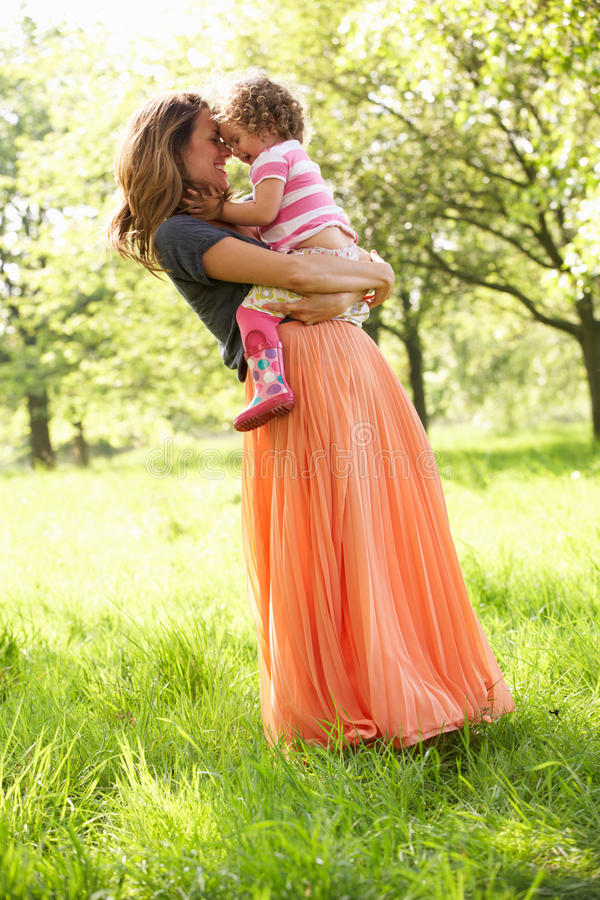 Mother Carrying Young Daughter royalty free stock image