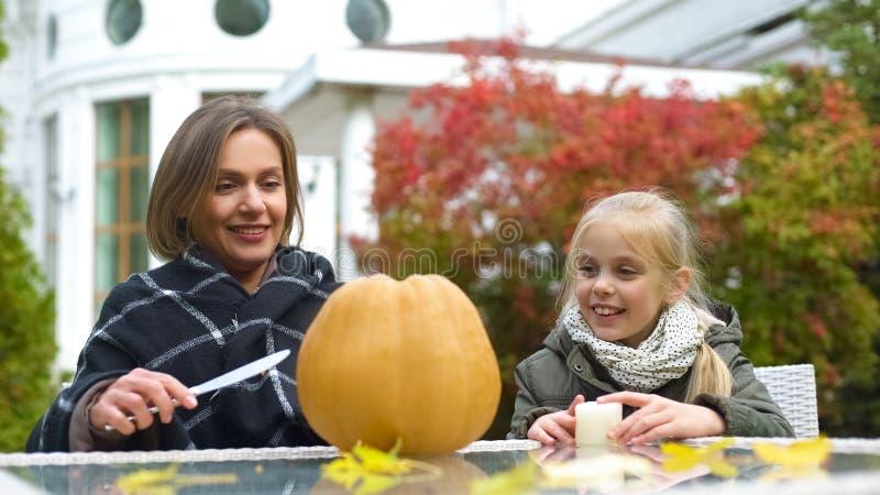Mother carves pumpkin jack-o-lantern, daughter holding candle, togetherness stock photography