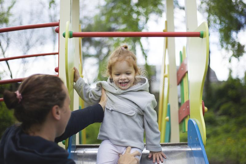 Mother catches daughter from a children slide, satisfied daughter contentedly on a children playground stock photo