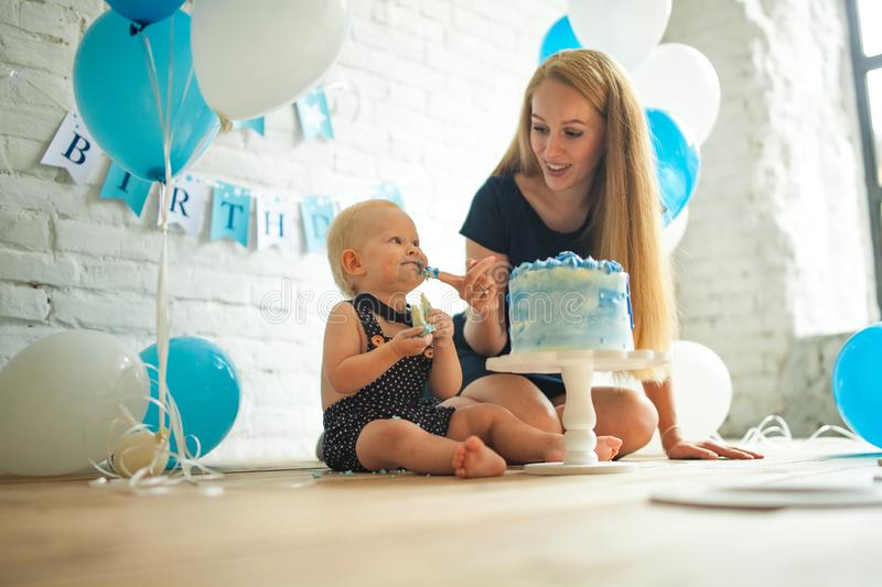 Mother is celebrating first birthday of her son and feeding his by cake. Mother is celebrating first birthday of her one year old son and feeding his by festive stock photos
