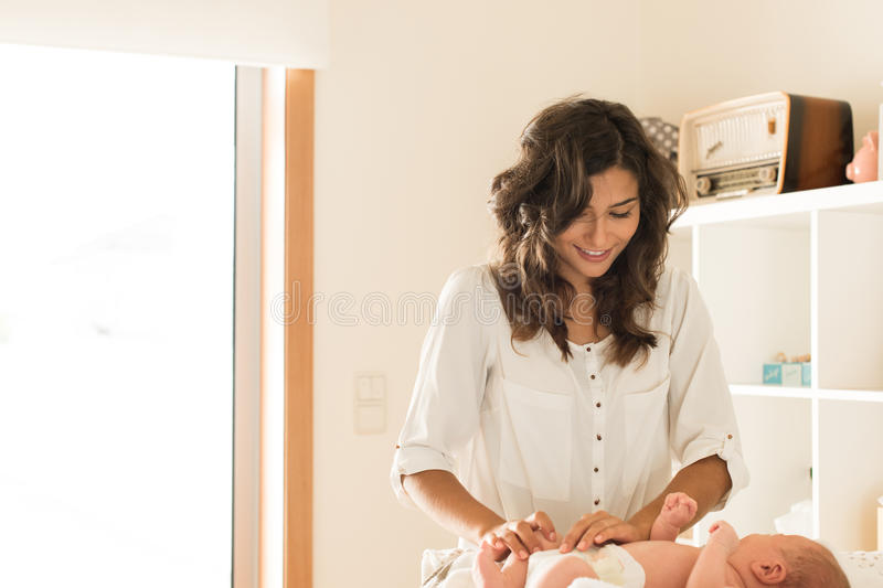 Mother changing baby`s diaper. Mother changing a diaper on newborn baby royalty free stock photography