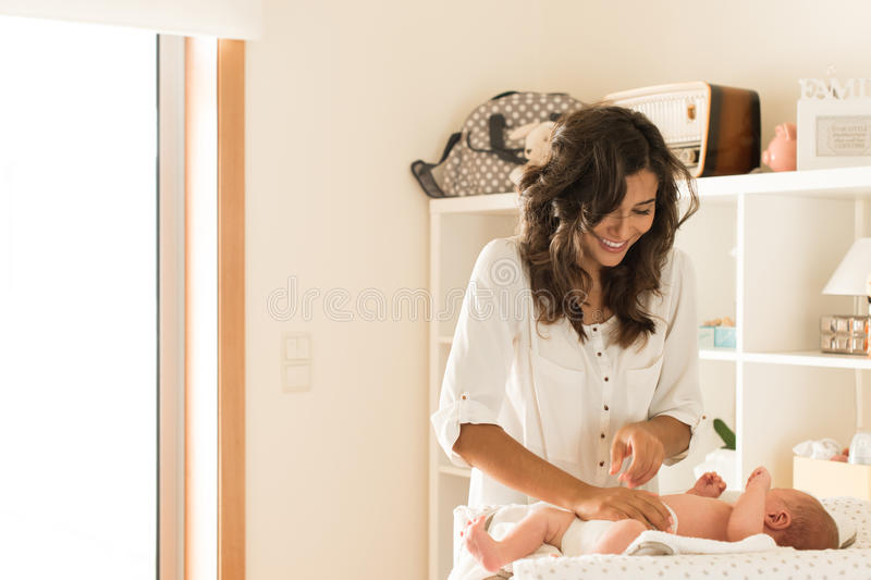 Mother changing baby`s diaper. Mother changing a diaper on newborn baby stock images