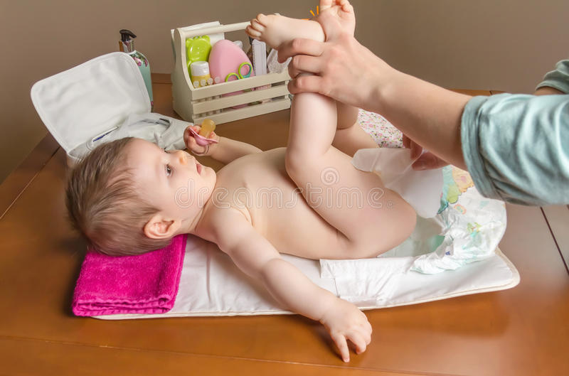 Mother changing diaper of adorable baby. With a hygiene set for babies on the background stock images
