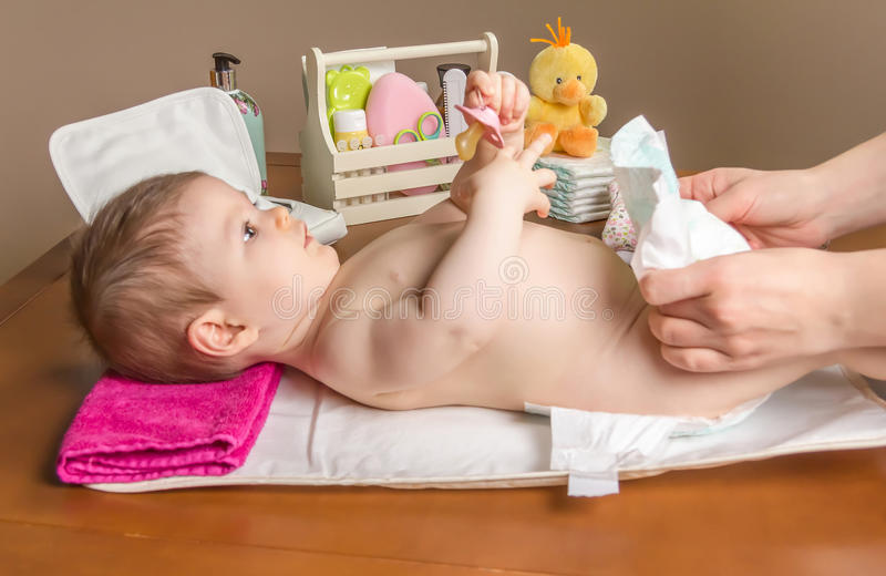 Mother changing diaper of adorable baby. With a hygiene set for babies on the background stock photo
