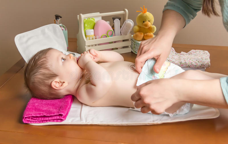 Mother changing diaper of adorable baby. With a hygiene set for babies on the background royalty free stock image