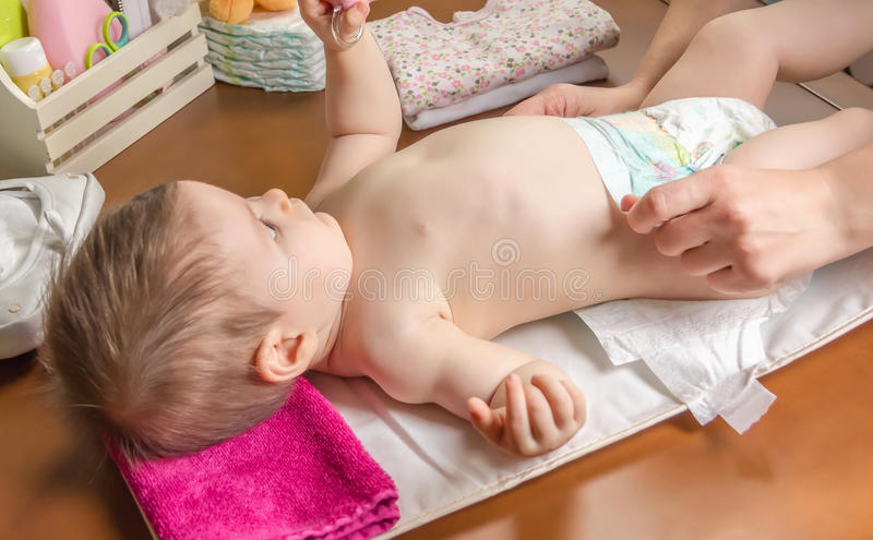 Mother changing diaper of adorable baby. With a hygiene set for babies on the background stock photos