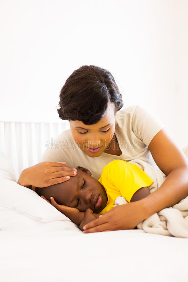 Mother checking son temperature. Loving african american mother checking her son temperature stock image