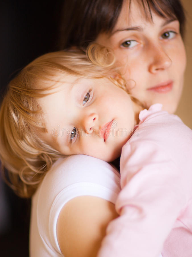 Mother with child. Sleepy little child with mom - shallow DOF, focus on little girl's eyes royalty free stock photos