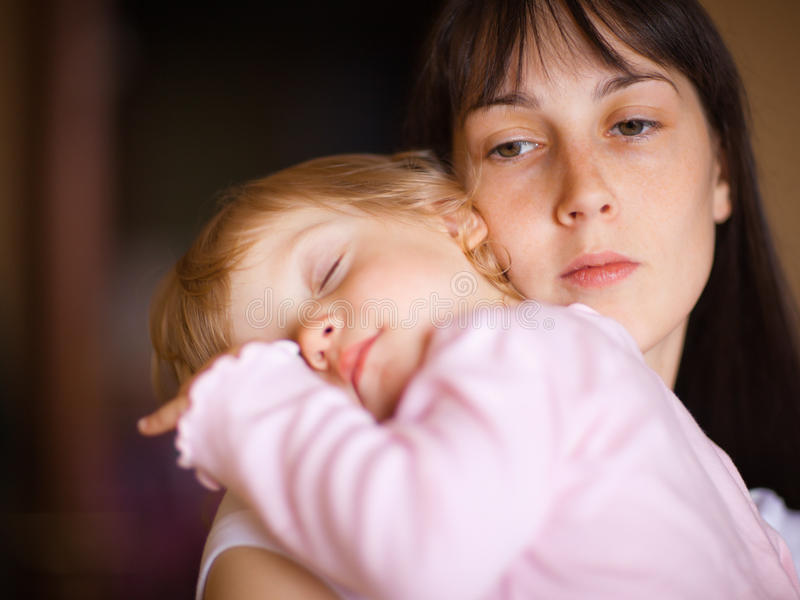 Mother with child. Sleepy little child with mom - shallow DOF, focus on woman's eyes royalty free stock images