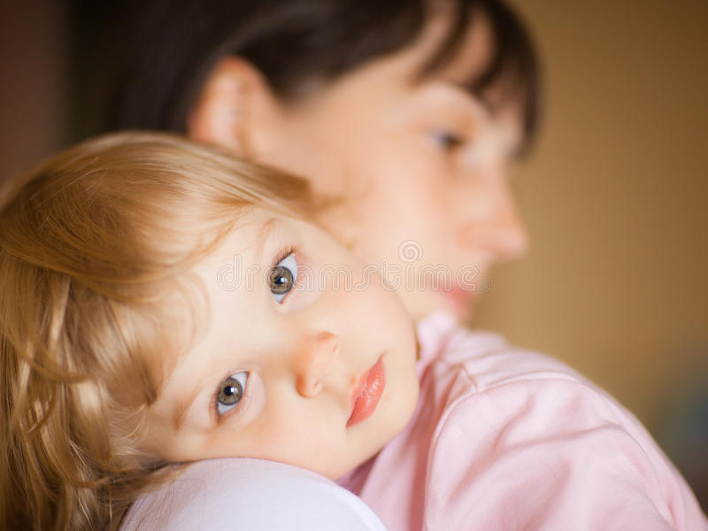 Mother with child. Sleepy little child with mom - shallow DOF, focus on eyes stock photography