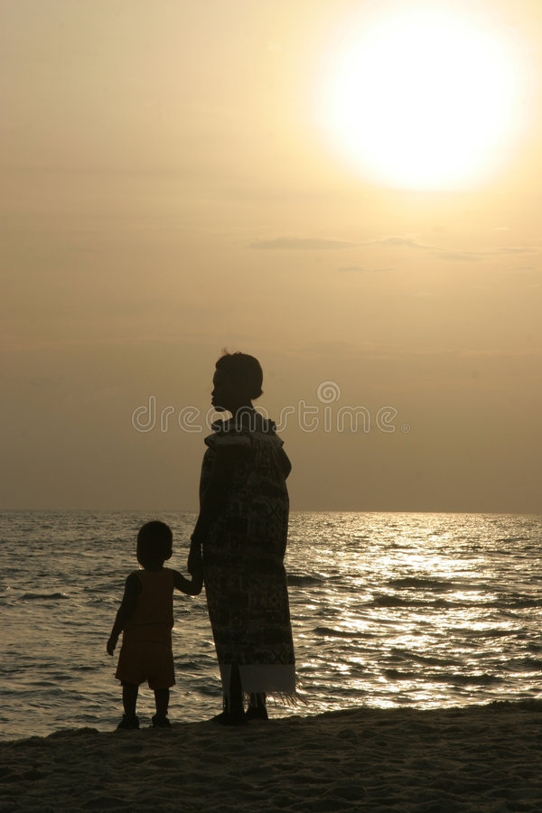 Mother and child. At sunset looking at the sea