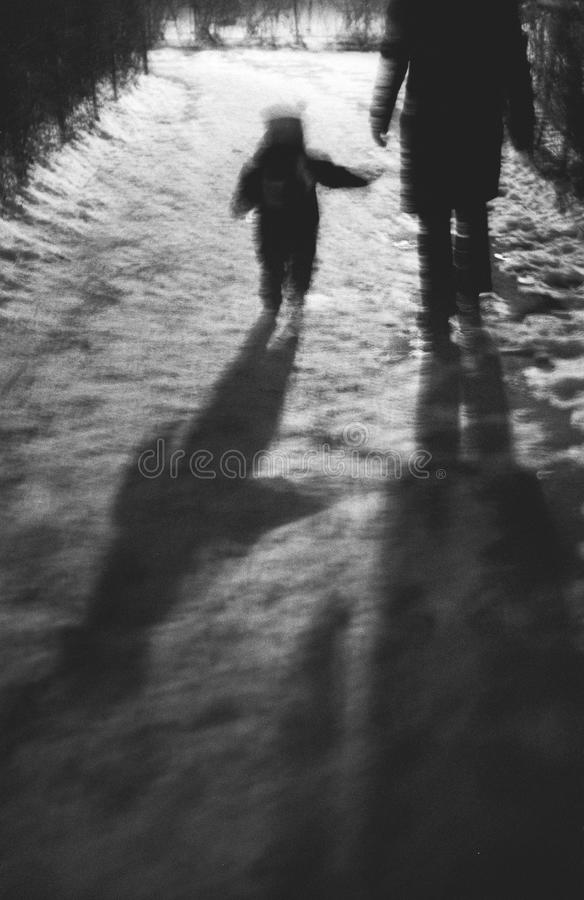 Mother and child abstract. Mother and child walking in snow, holding hands, motion blur, abstract image scanned from film royalty free stock image