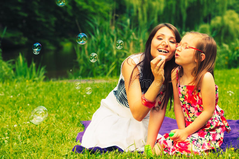 Mother And Child Blowing Soap Bubbles Outdoor. Stock Image