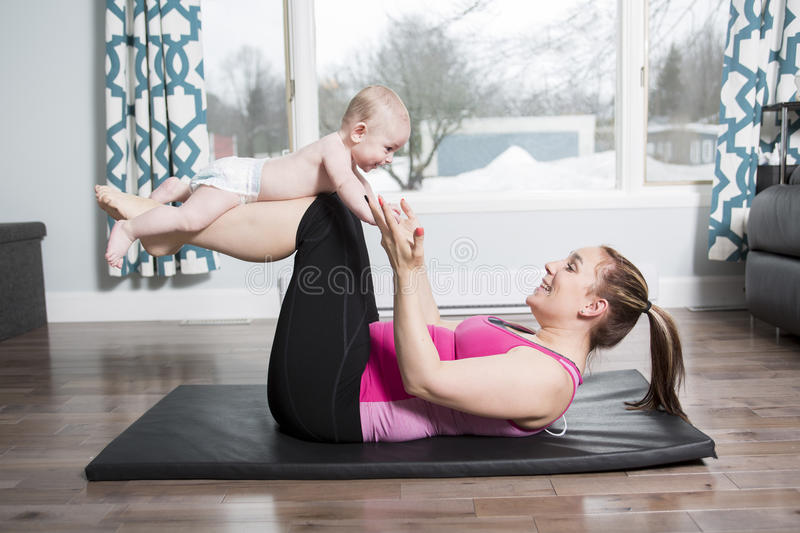Mother with child boy doing fitness exercises stock photos