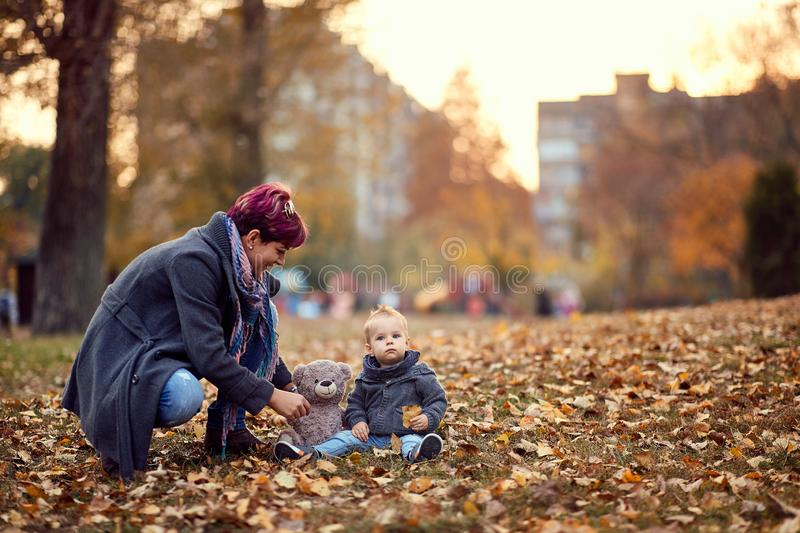 Mother and child playing, smiling and having fun in autumn city park. Bright yellow trees and leaves royalty free stock photo