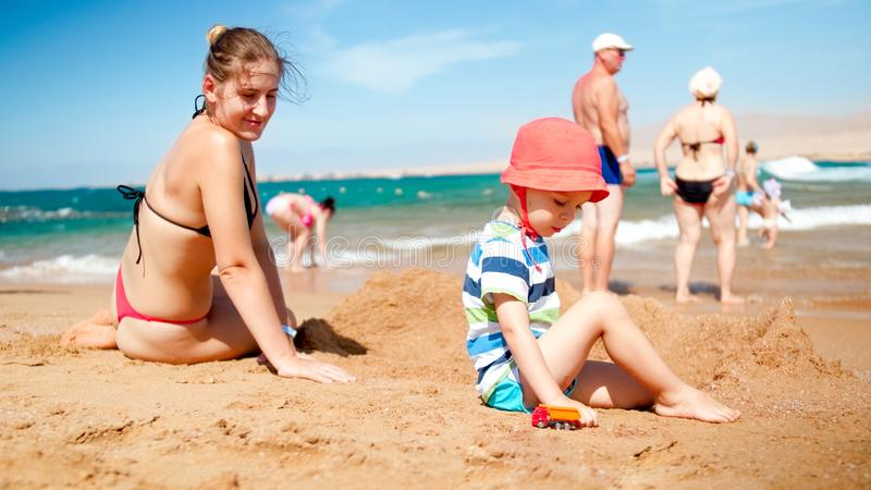 Mother with child boy sitting on the sandy beach and playing with toy cars. Family relaxing and having fun on the summer royalty free stock photography