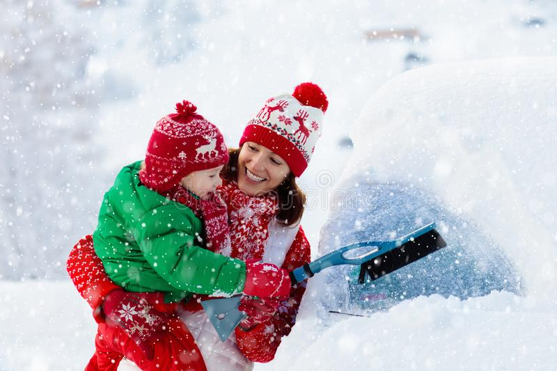 Mother and child brushing off car in winter royalty free stock photography