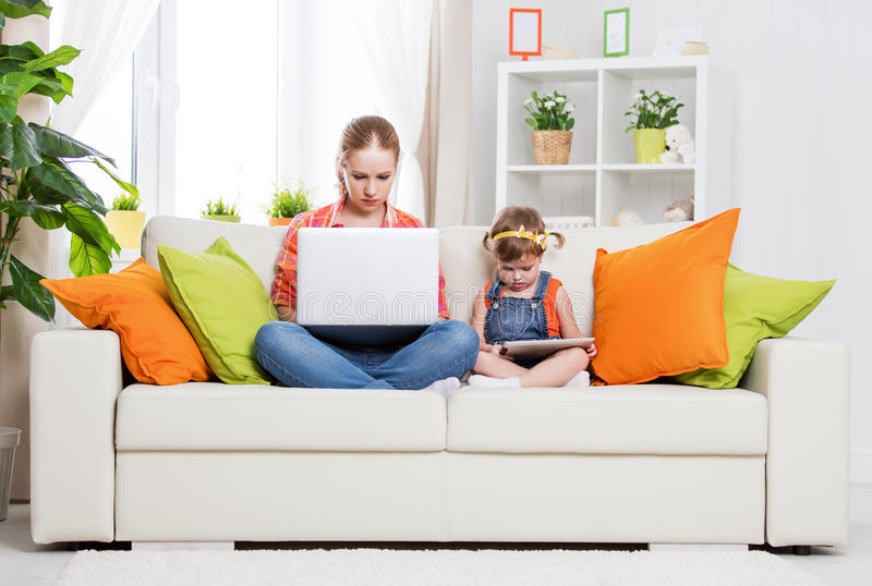 Mother and child with computer and tablet at home, according to stock images