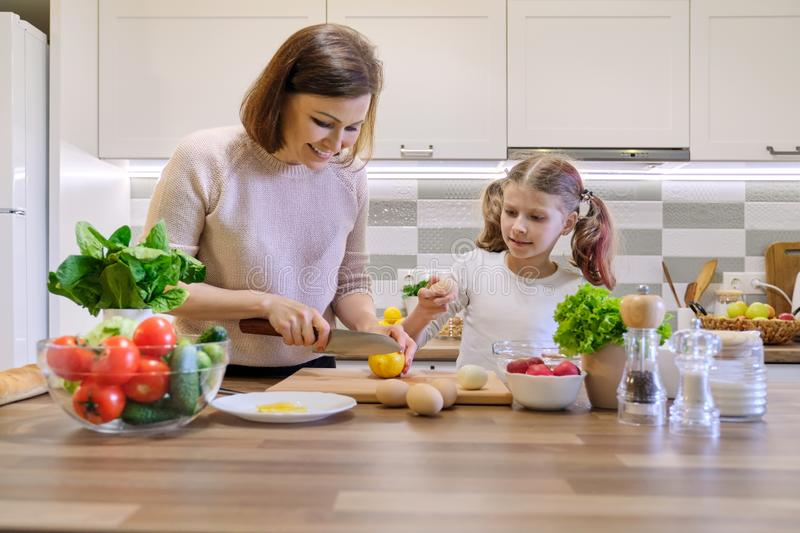 Mother and child cooking together at home in kitchen. Healthy eating, mother teaches daughter to cook, parent child communication stock images