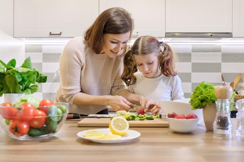 Mother and child cooking together at home in kitchen. Healthy eating, mother teaches daughter to cook stock photos