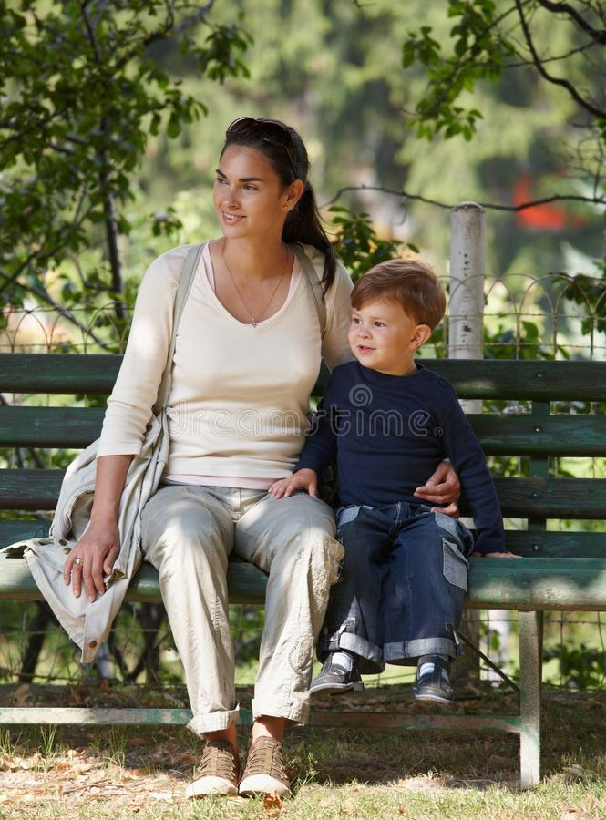 Mother and child cuddling sitting on bench royalty free stock photo