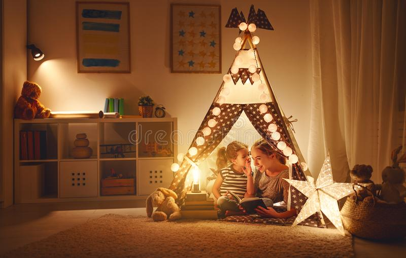 Mother and child daughter with a book and a flashlight before go stock photo