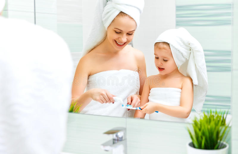 Mother and child daughter brush their teeth with toothbrush stock photo