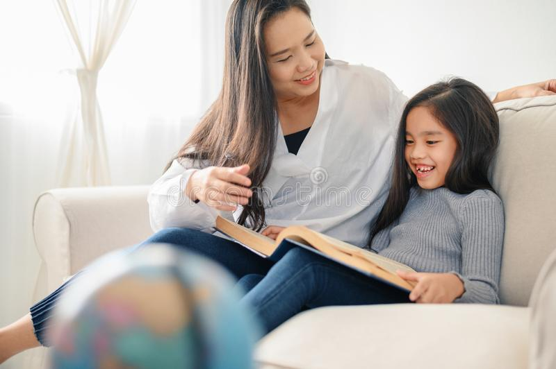 Mother and child daughter doing homework  and reading at home royalty free stock photo