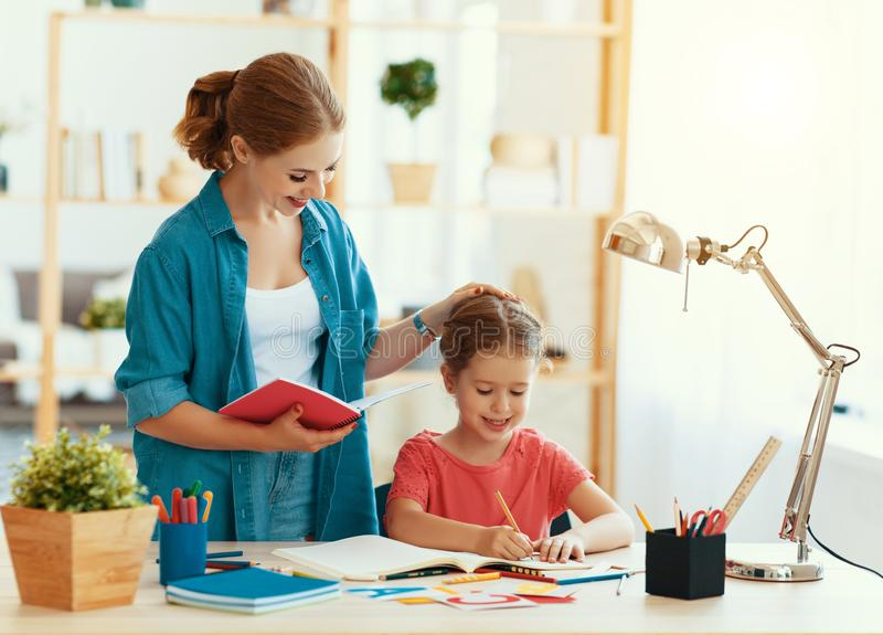 Mother and child daughter doing homework writing and reading. At home royalty free stock photos