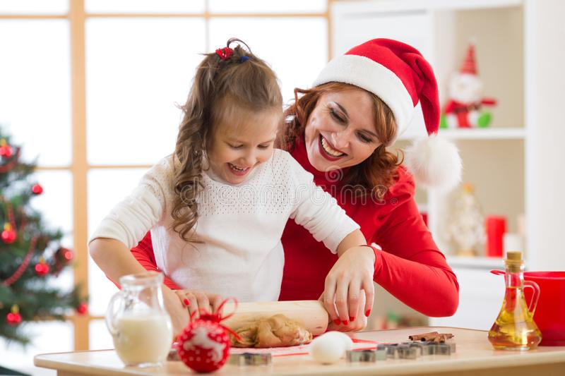 Mother and child daughter making christmas cookies and having fun. Focus on mother royalty free stock images