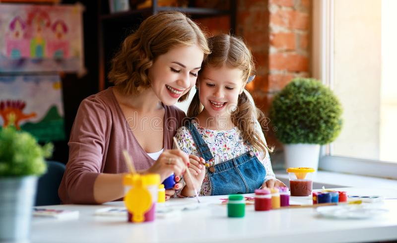 Mother and child daughter painting draws in creativity in kindergarten. Mother and child daughter painting draws are engaged in creativity in kindergarten royalty free stock images