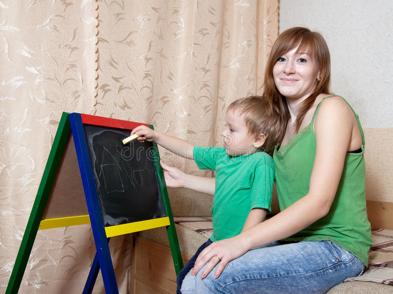 Download Mother And Child Draws On  Blackboard Stock Image - Image: 24436931