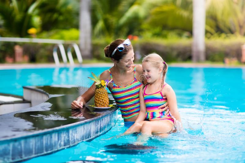 Mother and child drink juice in swimming pool royalty free stock image