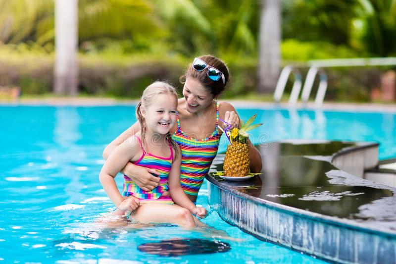 Mother and child drink juice in swimming pool royalty free stock images