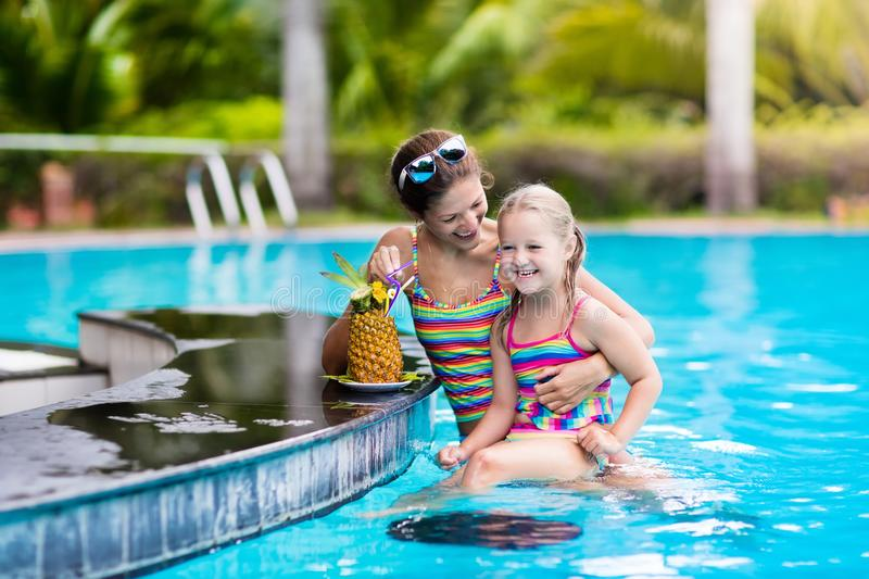 Mother and child drink juice in swimming pool royalty free stock photos