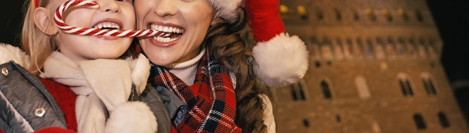 Mother and child eating Christmas candy cane in Florence, Italy royalty free stock images