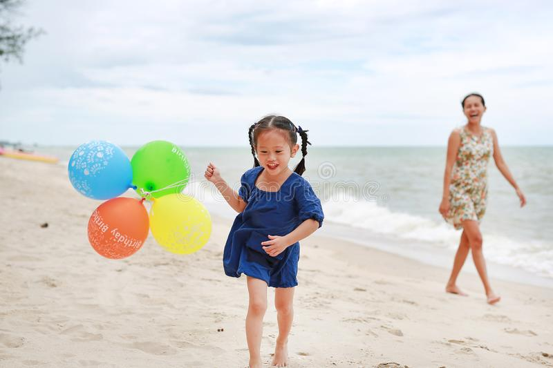 Mother and child girl on the beach with colorful balloons. Holiday concept royalty free stock image
