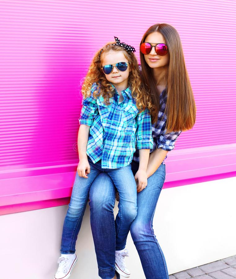 Mother and child girl in checkered shirts, sunglasses in city on colorful pink wall royalty free stock photo