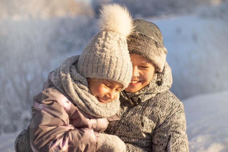 Mother and child girl having fun, playing and laughing on snowy winter. stock photography