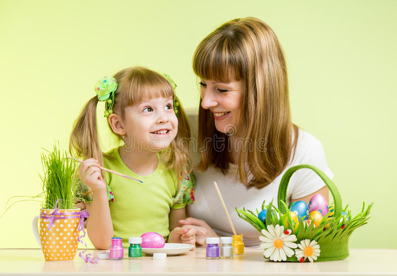 Mother with child girl play and paint easter eggs stock images