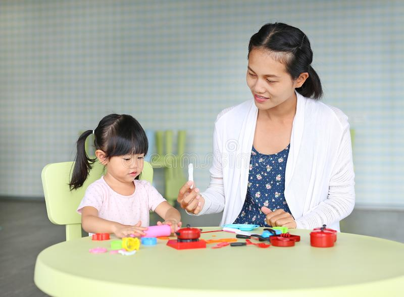 Mother and Child girl sitting at the table and plays artificial fruit stock photo