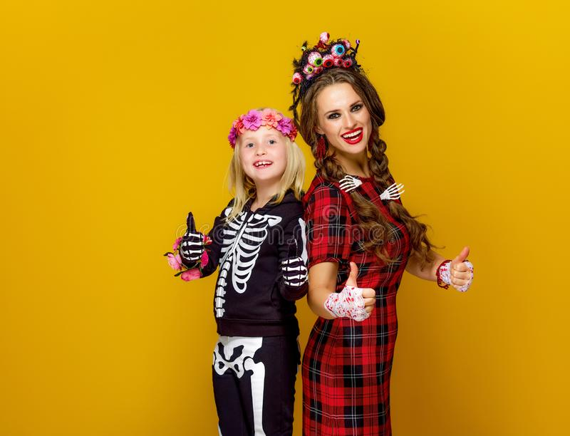 Mother and child in halloween costume showing thumbs up stock image