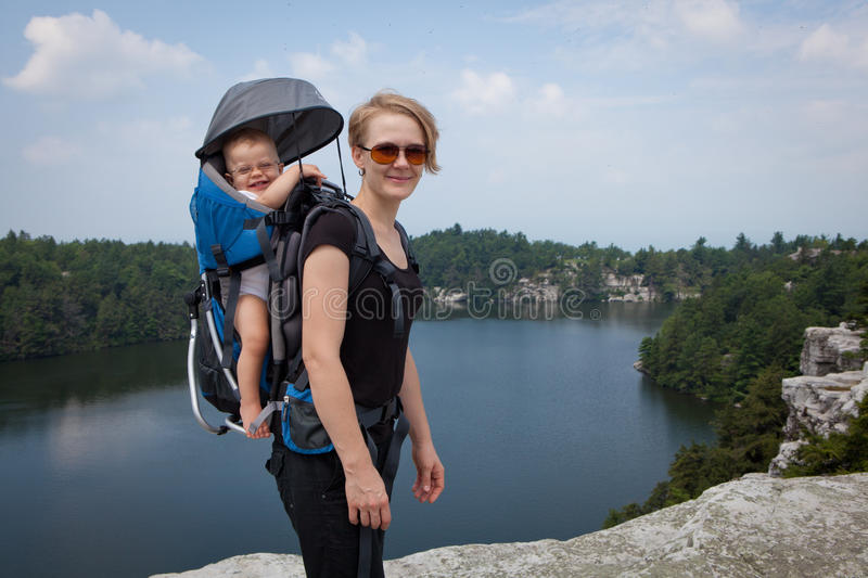 Mother and child on the hiking. Mother hiking with a small child in baby carrier royalty free stock image