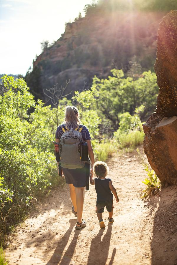 Mother and child hiking on a scenic mountain trail. Mother and child hiking together along a scenic mountain trail on a summer day. Lifestyle photo of people stock photos