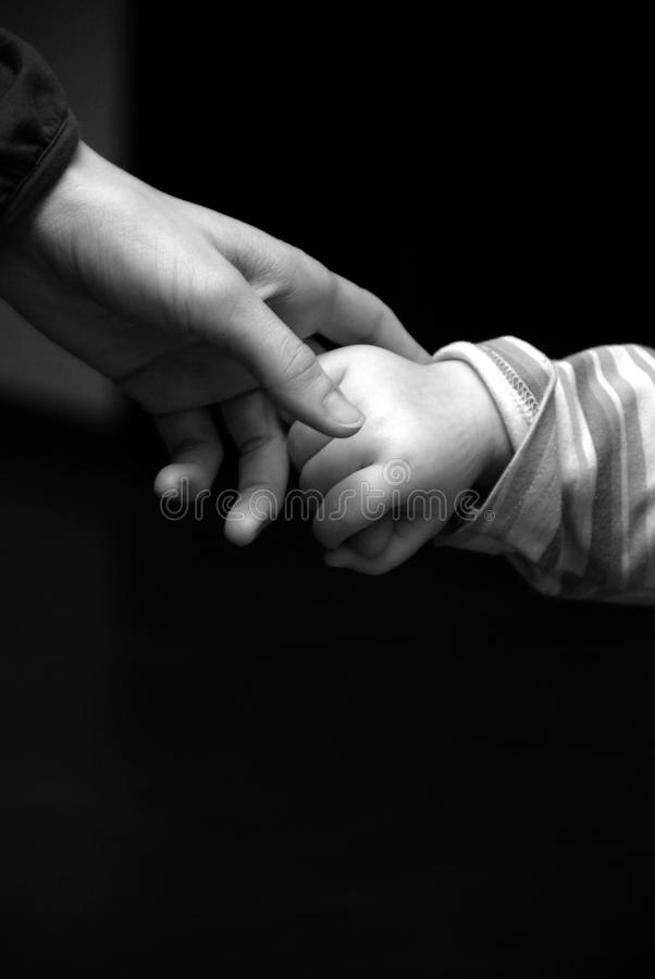 Mother and child holding hands in black and white royalty free stock photo