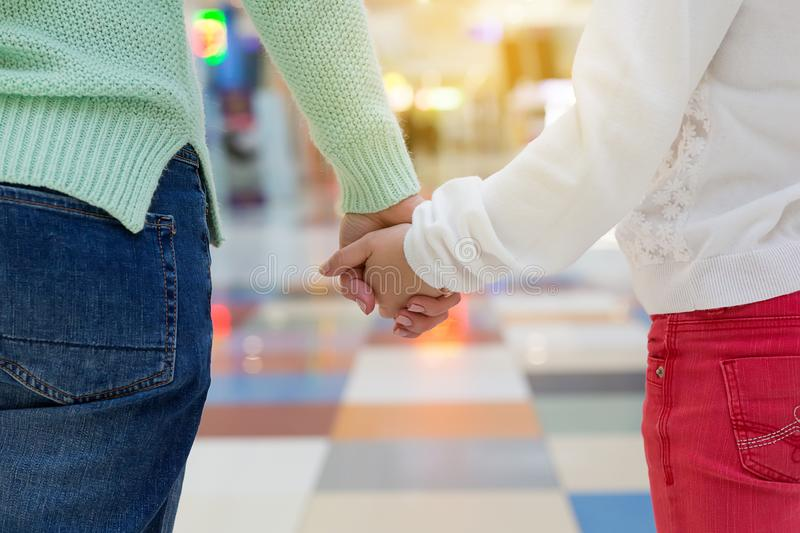 Mother and a child holding hands in shopping mall. Close up stock photos