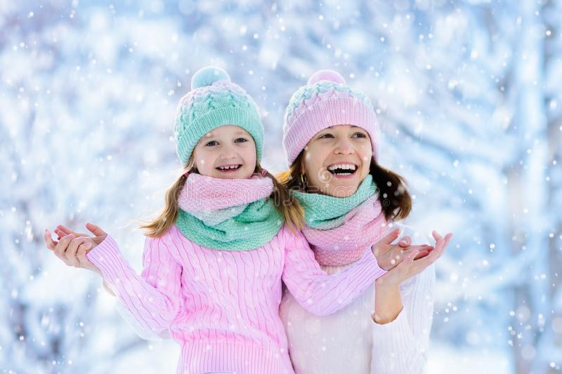 Mother and child in knitted winter hats play in snow on family Christmas vacation. Handmade wool hat and scarf for mom and kid. royalty free stock image