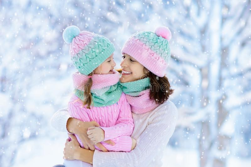 Mother and child in knitted winter hats play in snow on family Christmas vacation. Handmade wool hat and scarf for mom and kid. royalty free stock photography
