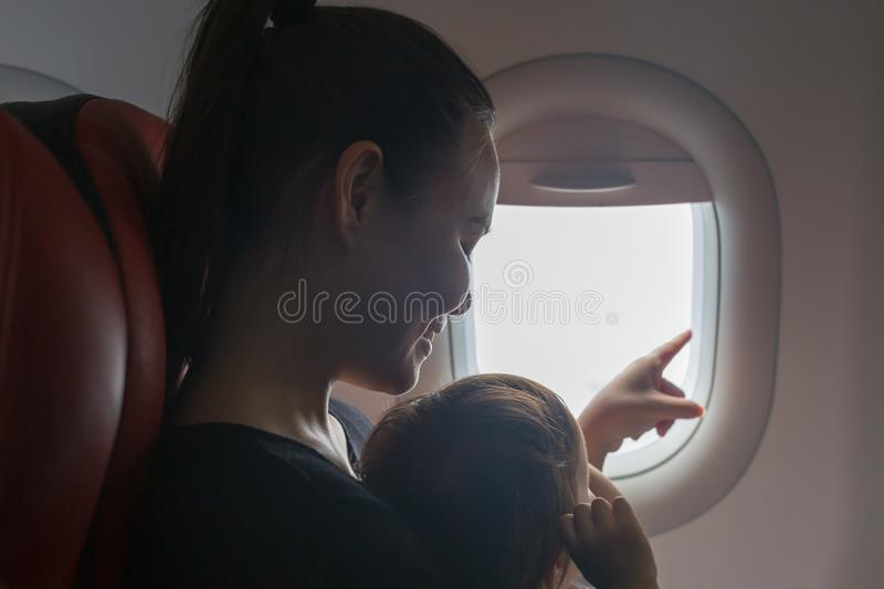 Mother and child looking out the window of an airplane. Traveling with kids. Family vacation. royalty free stock photos